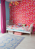 A second girl's bedroom is decorated with a vibrant floral wallpaper and has floor cushions stored under the wrought-iron bed