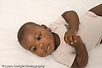 5 month old baby boy on back closeup portrait hands clasped at chest horizontal African American