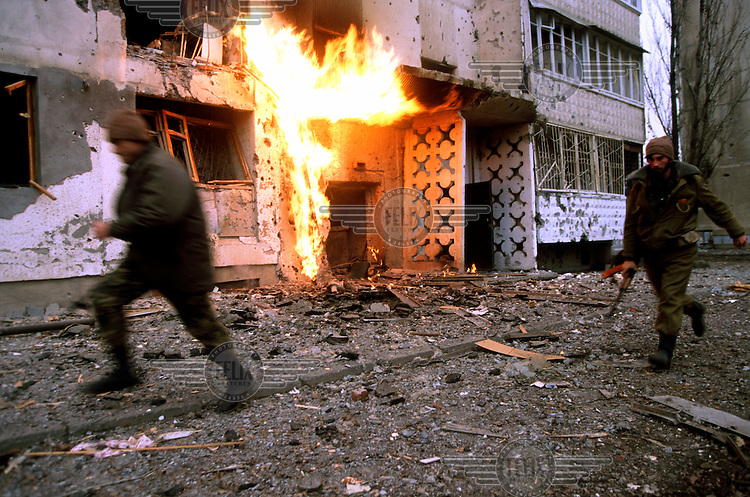 Chechen fighters move through the back streets of Grozny to their positions as a gas flame burns near the entrance to an apartment block after gas pipes were hit by shrapnel. Besieged residents later found ways to use the new free energy source for heat and light in the destroyed city.