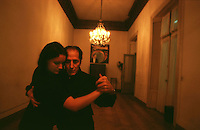 """With a photo of Carlos Gardel in the back, Maestro V?ctor, """"el Cacha"""", Pruno guides one of his students through the big dancing room of the National Academy of Tango in Buenos Aires, May 16, 2003. Photo by Quique Kierszenbaum"""