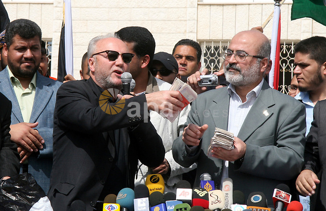 Hamas deputy prime minister Ziad al-Zaza holds up a bundle of British pounds received from British MP George Galloway (L) during a ceremony in Gaza City on March 10, 2009. Firebrand British MP George Galloway donated thousands of British pounds and dozens of vehicles to the Hamas-run government in the Gaza Strip after arriving in an aid convoy.  APAIMAGES PHOTO / Ashraf Amra