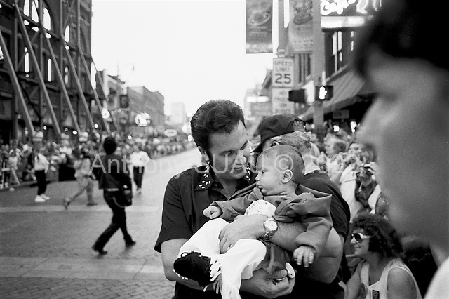Memphis, Tennessee<br /> USA<br /> August 10, 2002<br /> <br /> An Elvis look alike with his 4 month old son dressed as a baby King during a parade on Beale street to mark the 25 year anniversary of Elvis Presley's death.
