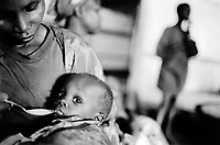 Burundi. Karuzi Province. Buhiga. The non-governmental organization (NGO) Médecins Sans Frontières (MSF) runs a  therapeutic feeding center (TFC) for malnourished children. A mother feeds her child with a spoon.© 2000 Didier Ruef