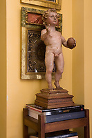 A stone figurine of a boy is displayed on a wooden table
