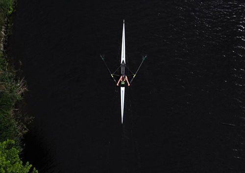 Overhead image of a solo rower on a river
