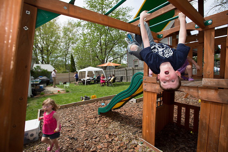 Benjamin plays on the monkey bars in his backyard during a party for him. Earlier that day he had his First Communion at St. Francis de Sales, the same church where Matthew had his First Communion.