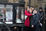 © Joel Goodman - 07973 332324 . 20/12/2017. Manchester, UK. Mourners hug and cry next to Sam's coffin in the hearse , outside the church after the service . The funeral of 14-year-old Sam Berkley at Christ Church in Denton , East Manchester . Mourners wear red and white , the colours of Hattersley FC , for whom Berkley played . Amongst their number are pupils and friends from Audenshaw School . Berkley died after being hit by a grey BMW near junction 3 of the M67 in Hyde , East Manchester , on 1st December 2017 . Photo credit : Joel Goodman