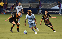 KANSAS CITY, KS - AUGUST 25: Gianluca Busio #27 of Sporting Kansas City drives the ball upfield as Christian Ramirez #13 and Memo Rodriguez #8 of Houston Dynamo attempt to stop him during a game between Houston Dynamo and Sporting Kansas City at Children's Mercy Park on August 25, 2020 in Kansas City, Kansas.