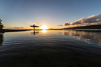 A surfer heading out for a sunset session is reflected in tide pools near Koko Head, East O'ahu.