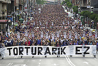 """Thousands of people attend a demonstration against torture on June 8, 2002, in Bilbao, Basque Country. The main banner reads in Basque language """"Torture no"""" and the little banners read """"6.000 people tortured"""". (Ander Gillenea / Bostok Photo)"""