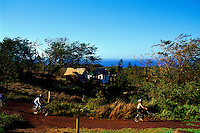 Bicyclists riding in Paniolo Camp with the Tentalow's in the background on Molokai Ranch