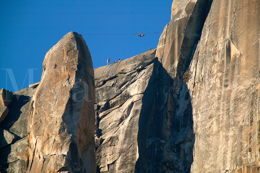 Climbers executing a tyrolean traverse  high above Yosemite Valley, Yosemite National Park, California.