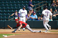 Carolina Mudcats first baseman Ryan Aguilar (11) stretches for a throw as Nick Madrigal (3) of the Winston-Salem Dash crosses the bag at BB&T Ballpark on June 1, 2019 in Winston-Salem, North Carolina. The Mudcats defeated the Dash 6-3 in game one of a double header. (Brian Westerholt/Four Seam Images)