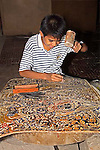Siem Reap, Cambodia_Cambodian young boy hammers nail into leather to carve shadow puppet_ an ancient tradition