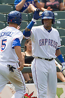 Round Rock Express outfielder Engel Beltre (7) greets teammate Alex Buchholz (5) after he scored in the seventh inning against the Colorado Springs Sky Sox in the Pacific Coast League baseball game on May 19, 2013 at the Dell Diamond in Round Rock, Texas. Colorado Springs defeated Round Rock 3-1 in 10 innings. (Andrew Woolley/Four Seam Images).