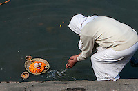 Nepal, Pashupatinath.  A Worshiper Places an Offering of Marigolds and a Candle into the Bagmati River.