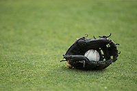A baseball and glove lie on the ground prior to the South Atlantic League game between the Greensboro Grasshoppers and the Kannapolis Intimidators at CMC-Northeast Stadium on June 9, 2015 in Kannapolis, North Carolina.  The Intimidators defeated the Grasshoppers 6-4.  (Brian Westerholt/Four Seam Images)