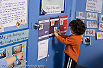 Education Preschool 3-4 year olds boy putting card for the weather on board signs in English and Spanish teacher's hand pointing toward board from left side horizontal
