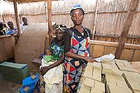 Africa, DRC, Democratic Republic of the Congo, South Kivu, Kamanyola. Women for Women project. WFW Kamanyola co-op and lifeskills training. Women making medicinal soap to sell.Sophia Asaku stacking the soap.