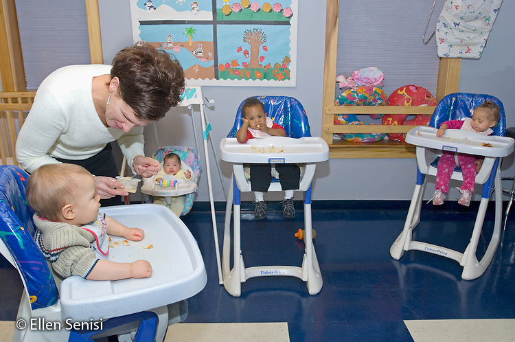 MR / Schenectady, NY.Schenectady Day Nursery / private non-profit daycare center / Infant Class.Teacher feeds infant (boy, 10 months) in high chair. Some other toddlers feed themselves. .MR: Kin6, Coo4, AF-SDNI.© Ellen B. Senisi