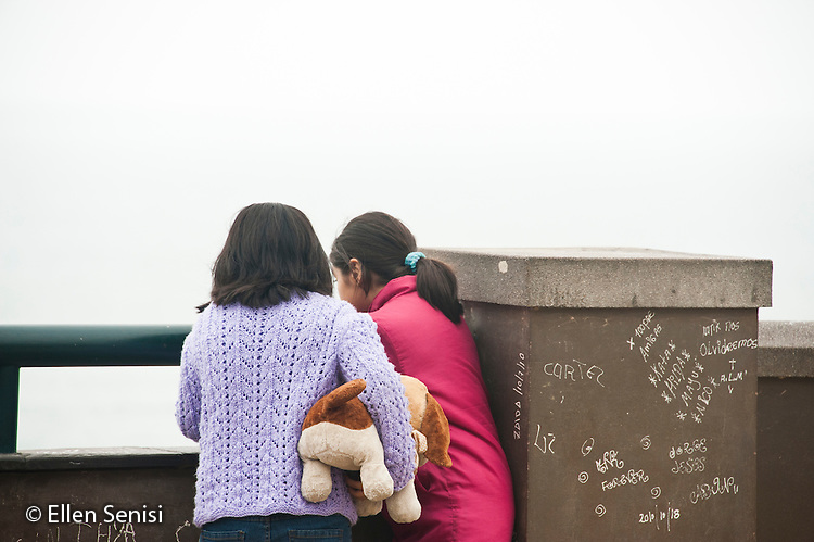 Lima, Peru. Miraflores district, Larcomar Mall. Two young girlfriends (Peruvian) look out at the water at viewpoint over the Pacific Ocean. No MR. ID: AL-peru.
