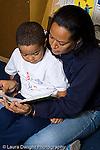 Preschool female parent volunteer reading to boy in classroom vertical
