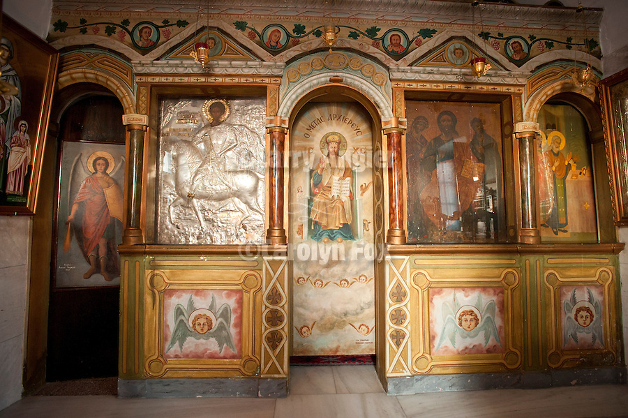 Iconostasis with icons os St. George and Jesus Christ sitting on throne in heaven on the iconostasis inside of a  Greek Orthodox church, Oia, Santorini, Greece