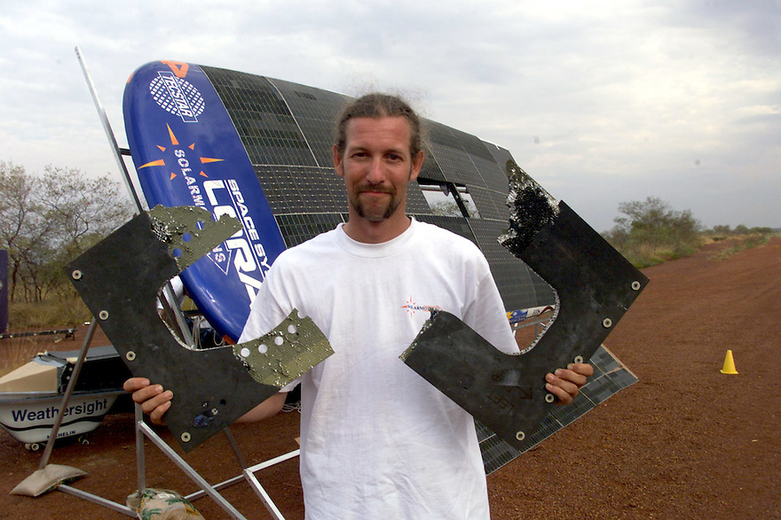 A solar car race driver shows damage to his vehicle after hitting road debris in the Australian Outback.