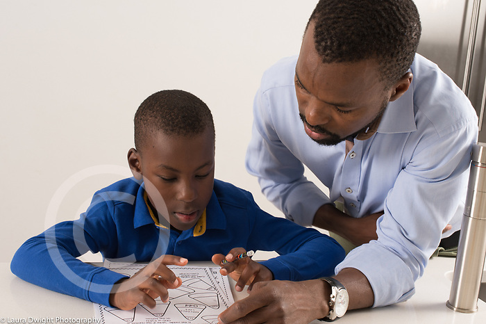 Seven year old boy at home, doing math assignment for homework, assisted by father