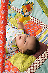 4 month old baby boy on back viewing dangled toys hand raised toward toy