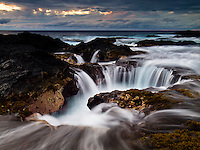 At sunset, the surging ocean fills holes along the Keahole Point shoreline on the Big Island.