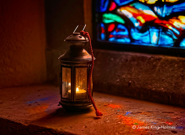A candle burns on a windowsill of St Lawrence Church, Tubney, Oxfordshire, UK