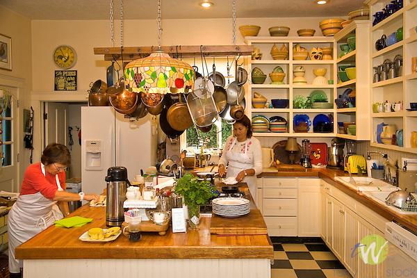 Clementine's Bed and Breakfast. Judith Markham in kitchen preparing popups with helper