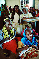 Sudan. West Darfur. Abu Zhar. Abu Zhar is located on a school compound in the town of Al Geneina and is a camp for internally displaced people (IDP)) from the civil war. A group of IDP girls, wearing colorful veils on the heads, seat in a classroom. They listen to the teacher and take notes from the words written on the blackboard. © 2004 Didier Ruef