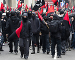 """© Joel Goodman - 07973 332324 . 26/03/2011 . London , UK . A black bloc of protesters carrying black and red anarcho-syndiclist flags walk from Blackfriars to Trafalgar Square . Hundreds of thousands of people attending an anti cuts demonstration under the banner """" March for the Alternative """" in central London , in protest at the coalition government's austerity measures . Photo credit : Joel Goodman"""
