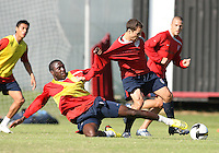 Josmer Altidore (yellow) slides the ball away from Steve Cherundolo during a practice session for the US men's national team at RFK auxiliary field on October 7, 2008 in Washington D.C. prior to the World Cup qualifying match against Cuba.