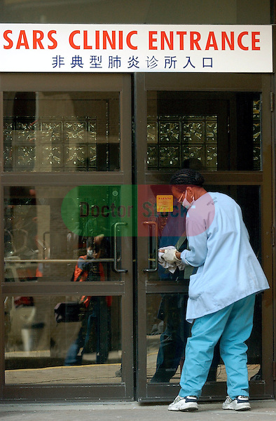 NOT MODEL RELEASED; FOR EDITORIAL USE ONLY... hospital worker wearing face mask disinfecting the door handles leading to the lobby of a Toronto SARS clinic