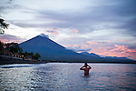 A swimmier enjoys a dip below Gunung Agung on the western part of Bali, Indonesia. The top of Gunung Agung is often clouded over.