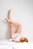Young red haired woman laying in bed with legs up on wall