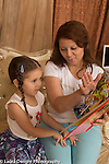 4 year old girl with mother, looking at book and listening to her explanation
