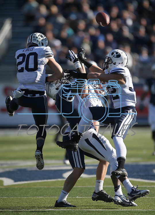 Nevada's Brandon Wimberly (1) tries to catch a pass while being surrounded BYU defenders Craig Bills (20), Daniel Sorensen (9) and Mike Hague (32) during the first half of an NCAA college football game in Reno, Nev., on Saturday, Nov. 30, 2013. (AP Photo/Cathleen Allison)