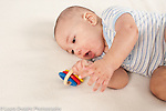 5 month old baby boy turing on side grasping wooden toy with moving colorful rings