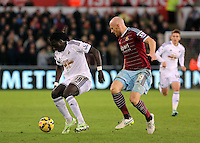 Pictured L-R: Bafetimbi Gomis against James Collins of West Ham Saturday 10 January 2015<br /> Re: Barclays Premier League, Swansea City FC v West Ham United at the Liberty Stadium, south Wales, UK
