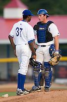Burlington catcher Tom Hill (44) goes over strategy with Yensi Lopez (37) versus Bluefield at Burlington Athletic Park in Burlington, NC, Monday, August 6, 2007.