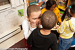 Education Preschool Headstart 3 year olds boy whispering secret to a friend, teacher and other children in background