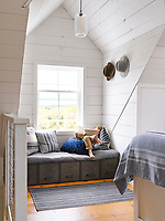 The upstairs loft houses the white, wood panelled master bedroom. The room is light and airy with its vaulted ceiling and the simple blue and white theme gives the space a cool feel. A window seat with drawers below provides extra storage.
