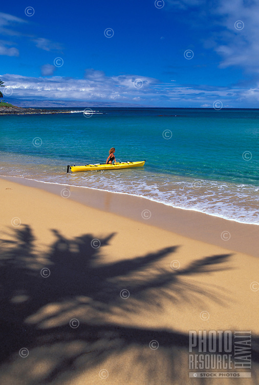 A woman in black heads out with a yellow kayak at Napili Bay, Maui.