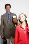 A young woman on a cell phone with a business man blurred in the background