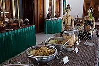 Yogyakarta, Java, Indonesia.  Javanese Buffet Lunch with Figures Representing Javanese Bride and Groom at end of Table.  Ndalem Ngabean Restaurant.