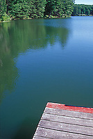 End of pier and reflections of trees in lake<br />